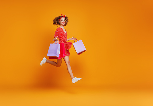 istock concept of shopping purchases and sales of happy   girl with packages  on yellow background 1161171039