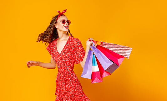 istock concept of shopping purchases and sales of happy   girl with packages  on yellow background 1164976534