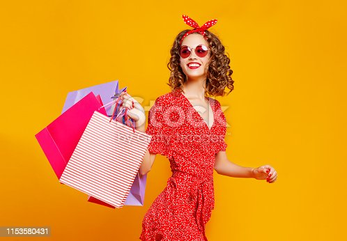 istock concept of shopping purchases and sales of happy young girl with packages  on yellow background 1153580431