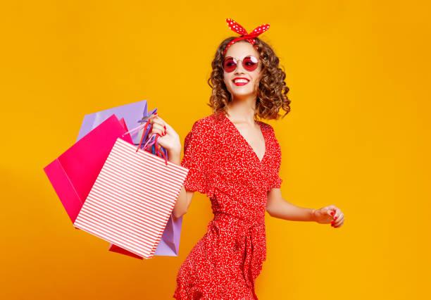 Konzept der Einkaufskäufe und Verkauf von glücklichen jungen Mädchen mit Paketen auf gelbem Hintergrund – Foto