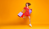 concept of shopping purchases and sales of happy young girl with packages in red dress on yellow background