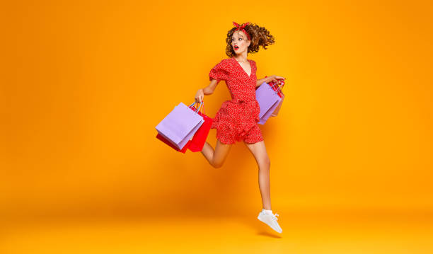 concept of shopping purchases and sales of happy young girl with packages  on yellow background - fashion стоковые фото и изображения