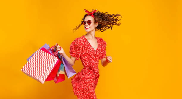concept of shopping purchases and sales of happy young girl with packages  on yellow background - jumping zdjęcia i obrazy z banku zdjęć