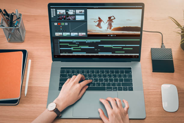 Concept of simple operation of blogger and vlogger, hand using laptop on video editor works with footage on wooden table, camera and accessories on table. stock photo