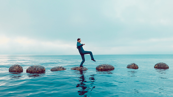 Man walks carefully on a path of small rocks in the middle of the sea. He looks focused and moves in the right direction. Concept of success and avoiding problems on the way of a journey or career path.  Note: The man is a 3D-render with face scan. Model release attached.