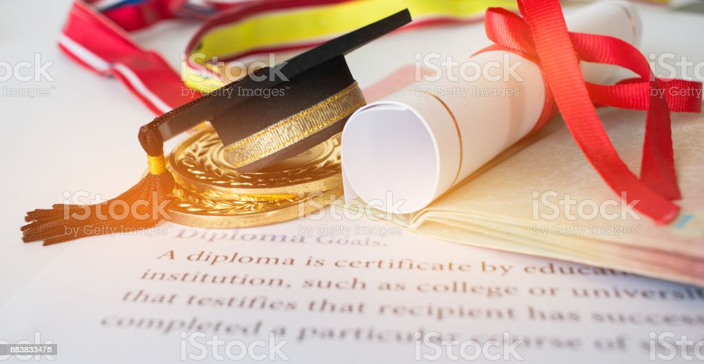 Concept of Success international education, graduation black cap on roll up Dollars bill, on letters diploma, medals and passport for work and studying, competition on abroad in famous institution. stock photo