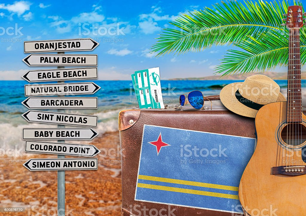 Concept of summer traveling with old suitcase and Aruba town foto de stock royalty-free