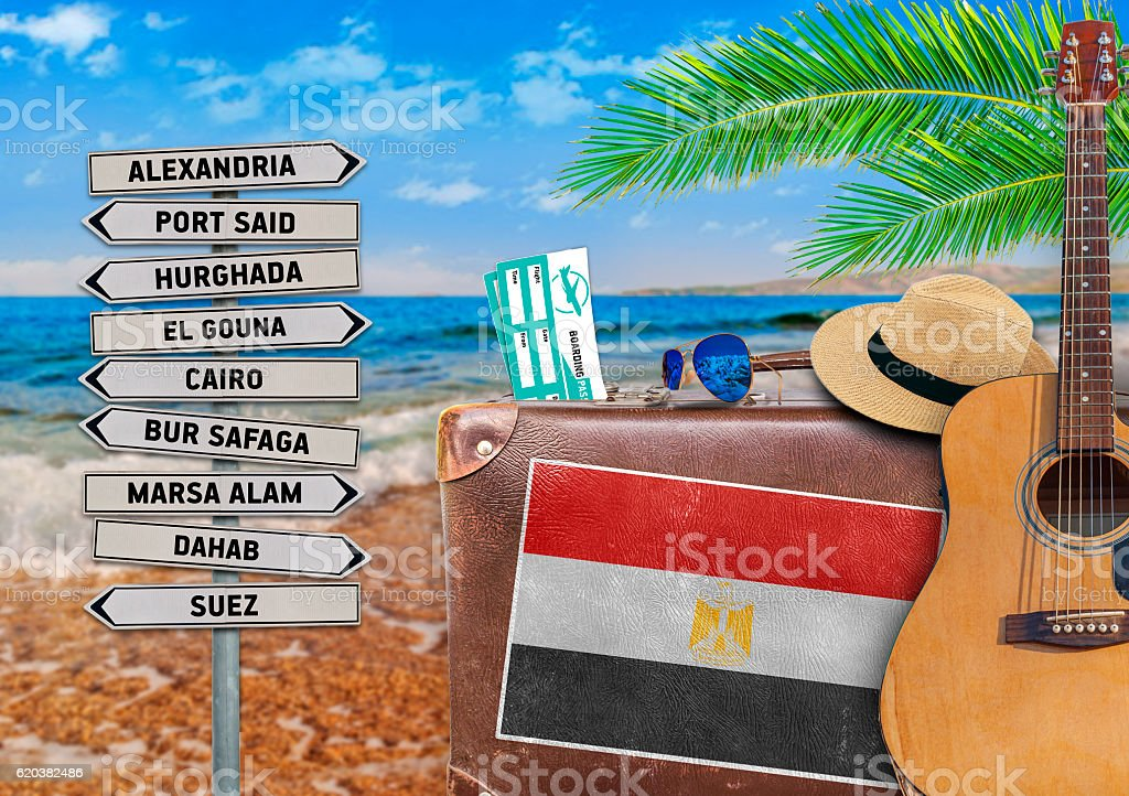 Concept of summer traveling with old suitcase and Egypt town stock photo