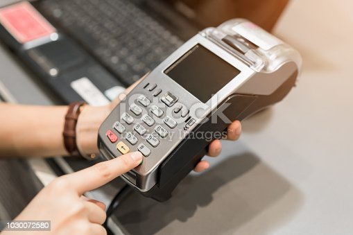 914593772istockphoto Concept of technology in buying without using cash. Close up of hand use credit card swiping machine to pay. 1030072580