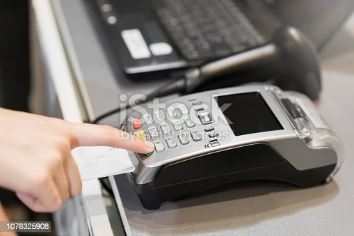 914593772istockphoto Concept of technology in buying without using cash. Close up of hand use credit card swiping machine to pay. 1076325908