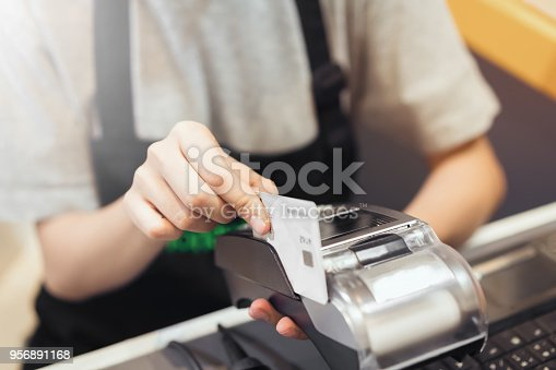 914593772istockphoto Concept of technology in buying without using cash. Close up of hand use credit card swiping machine to pay. 956891168