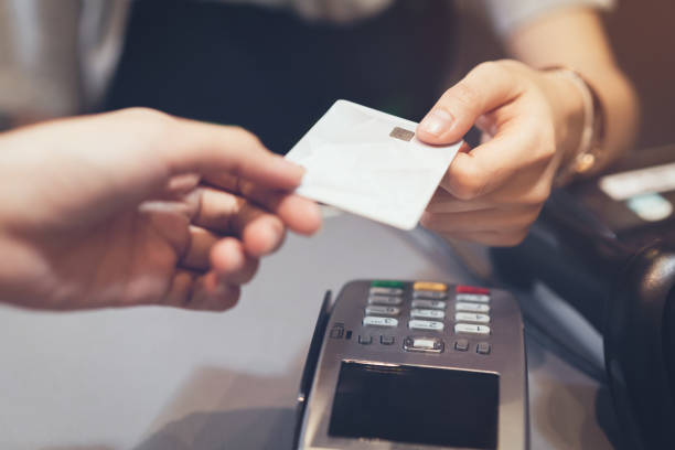 concept of technology in buying without using cash. close up of hand use credit card swiping machine to pay. - paying with card imagens e fotografias de stock