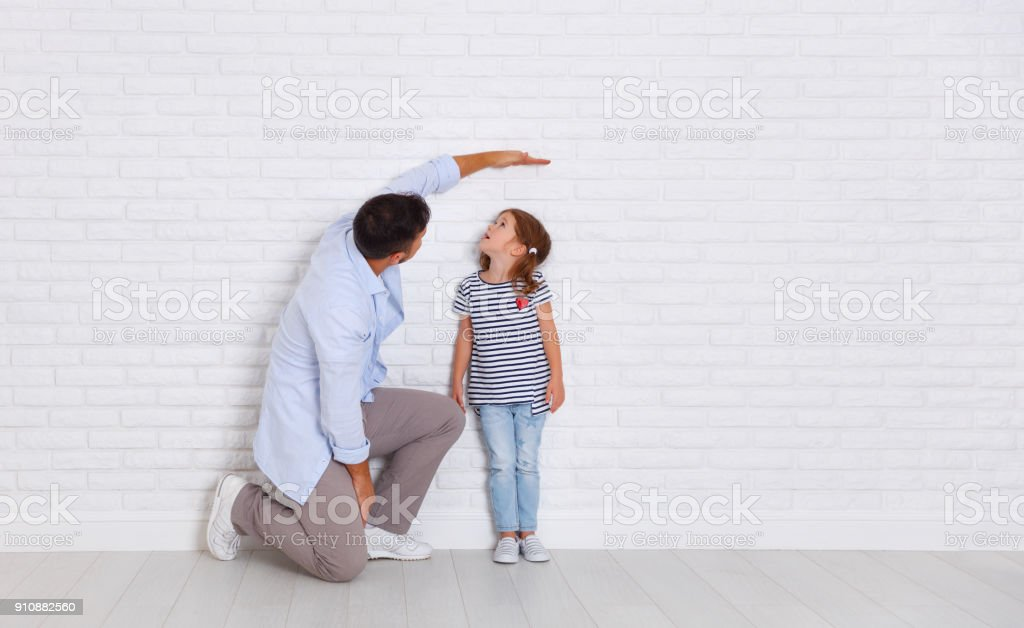 concept of the family. the father measures growth of child to daughter near empty wall stock photo