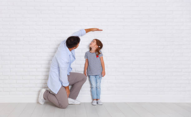concept of the family. the father measures growth of child to daughter near empty wall - high up stock photos and pictures