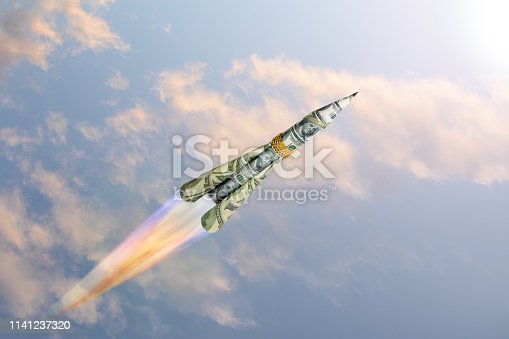 Concept of raising the dollar high in the sky in the form of a rocket