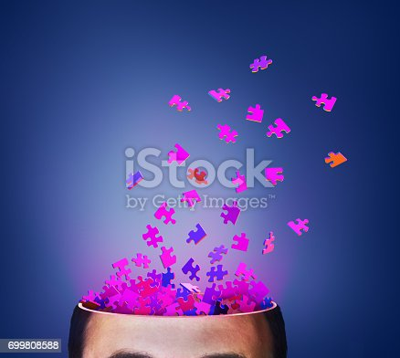 862650404istockphoto Concept of thinking. Brainstorm. Parts of puzzle exploding from cut of head. 3d illustration 699808588