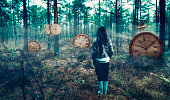 Woman stand in the middle of a foggy forest. There are big clocks scattered all around. Concept of time and chosing your right path.