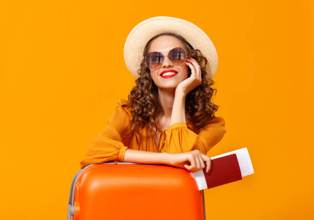 concept of travel. happy woman girl with suitcase and  passport on  yellow background - jumping zdjęcia i obrazy z banku zdjęć