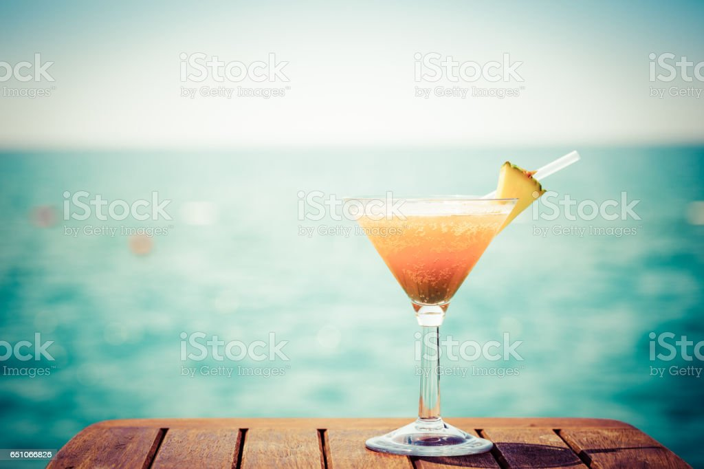 Concept of tropical vacation. Exotic cocktail on the pier. Luxury holiday background. Orange cocktail with sea view stock photo