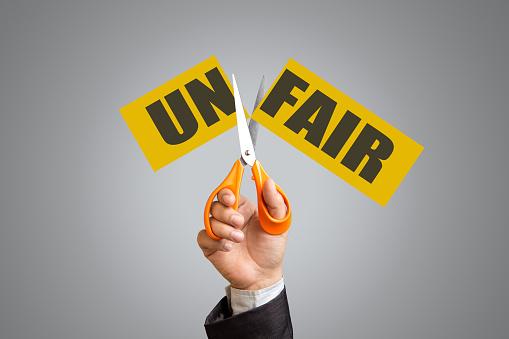 Businessman holding scissors cutting word unfair to fair
