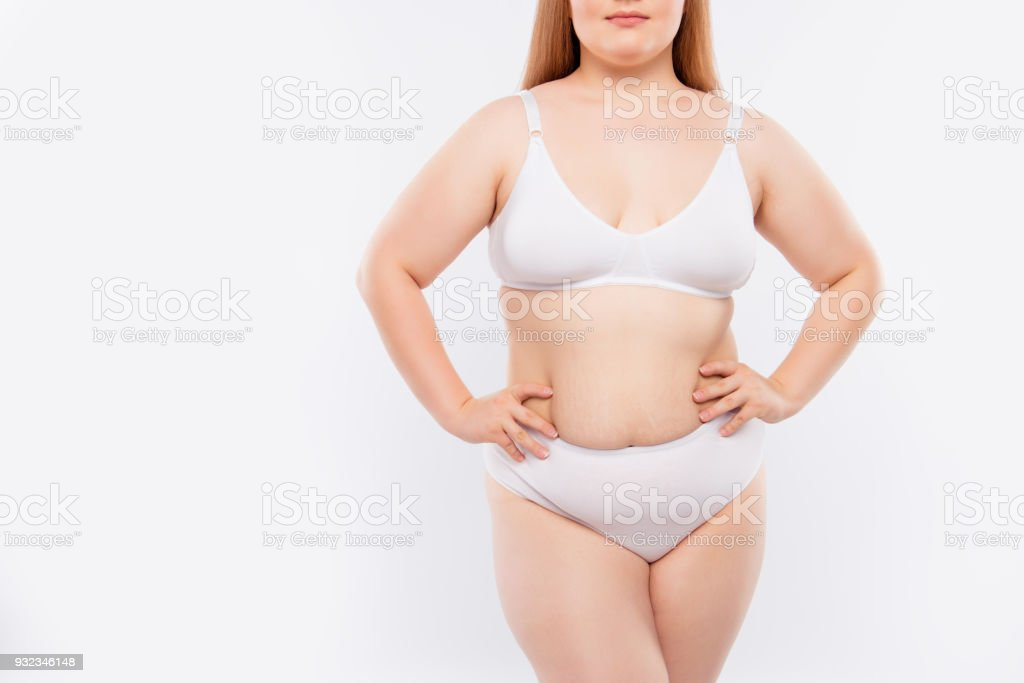 Concept of using lotion, cream, gel against cellulite and stretch marks. Cropped photo of chubby fatty with excess skin model's body, all the flaws are shown, isolated on white background, copy-space stock photo