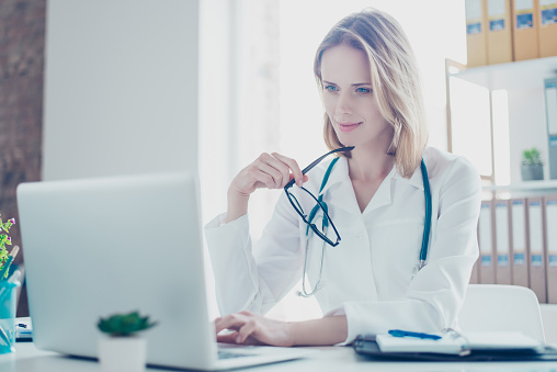 Concept of using modern technology at hospitals. Portrait of smiling charming female doc with glasses in hands, she is using her laptop for writing prescriptions