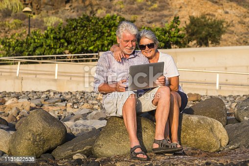 452783143 istock photo concept of vacation, technology, tourism, travel and people - happy senior couple with tablet pc computer on pebble beach. White hair and silver society with technology devices internet connected 1131622538