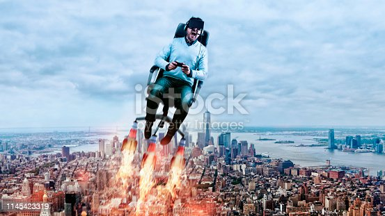 Man sits in office chair with rockets attached. He wears virtual reality glasses and holds on to a game controller. He flys through the air and screams because of the immersive gaming experience. New York City is in the background.