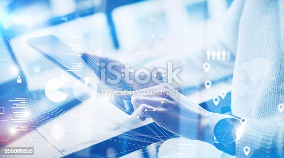 istock Concept of virtual screen,digital connection icon and graph interfaces.Young businesswoman working on modern mobile tablet while sitting at work place at sunny office.Blurred background. 855066856