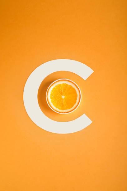 conceito de vitamina c, a laranja e a letra c em um fundo laranja - c - fotografias e filmes do acervo