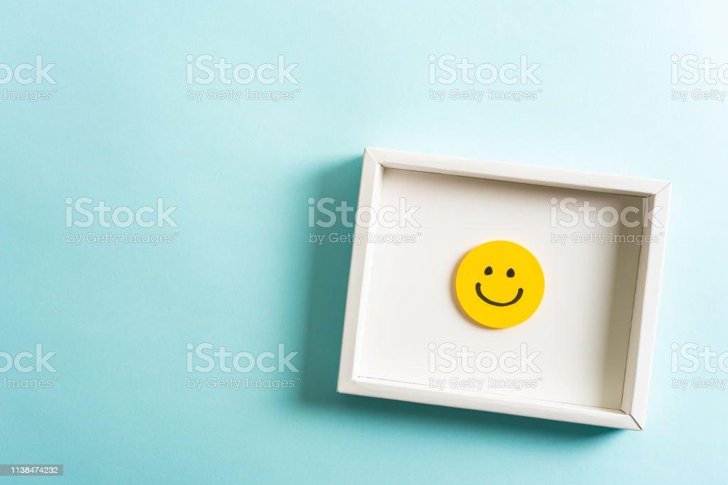 Konzept des Wohlbefindens, gut gemacht, Feedback, Mitarbeiteranerkennung. Fröhlich gelb lächelnder Emoticon-Gesichtsrahmen, der auf blauem Hintergrund mit leerem Platz für Text hängt. - Lizenzfrei Abstrakt Stock-Foto