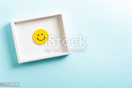 istock Concept of well-being, well done, feedback, employee recognition award. Happy yellow smiling emoticon face frame hanging on blue background with right empty space for text. 1171328428