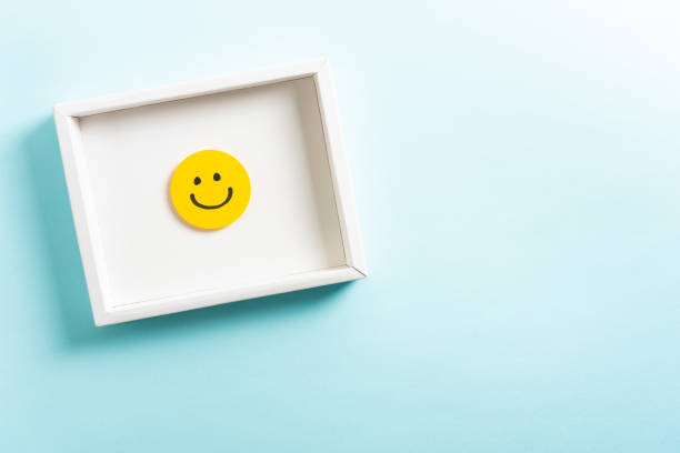 concept of well-being, well done, feedback, employee recognition award. happy yellow smiling emoticon face frame hanging on blue background with right empty space for text. - smiley antropomorfico foto e immagini stock