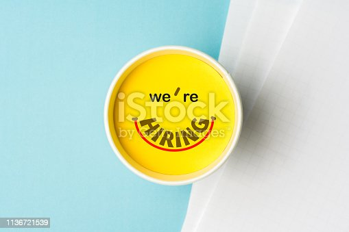477419728istockphoto Concept of we're hiring or join our team or onboarding process. Paper cup with yellow top and text we're hiring illustrating a happy face emoticon, all this on a desk with blank documents over blue background. 1136721539