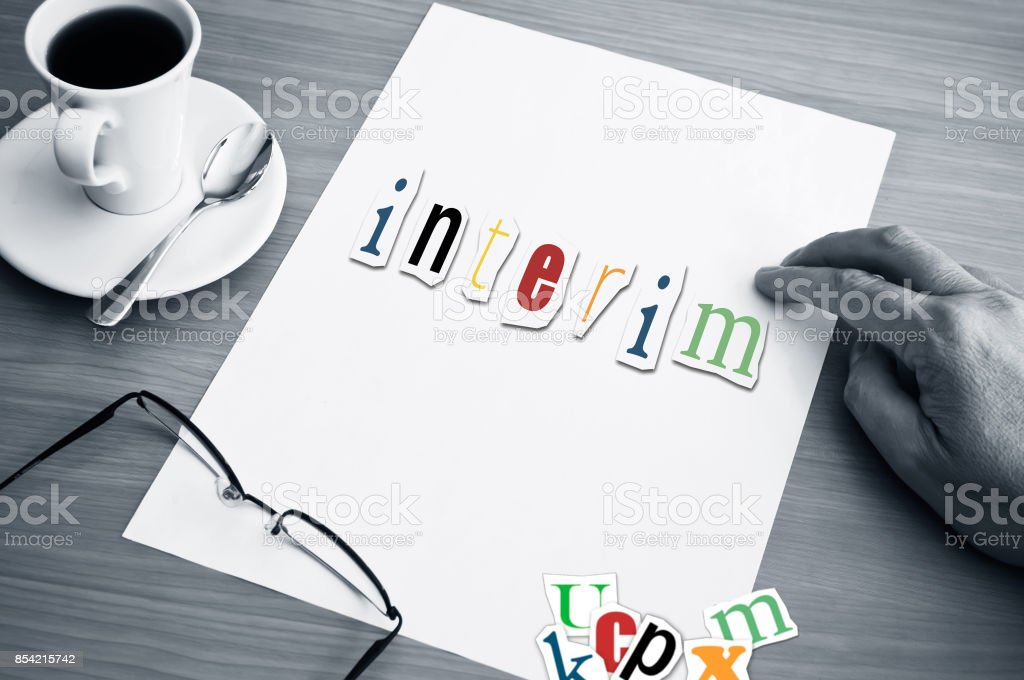 concept office cup of coffee and word interim on white page stock photo