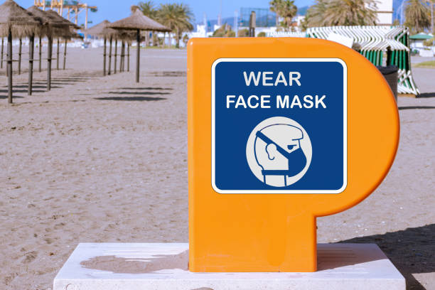 Concept on coronavirus, orange first aid emergency kit equipment on a beach with 'wear face mask' written on. Parasols and beach in background. stock photo