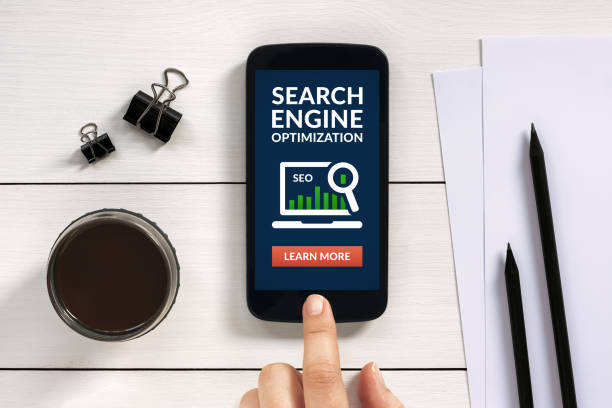SEO concept on smart phone screen with office objects stock photo