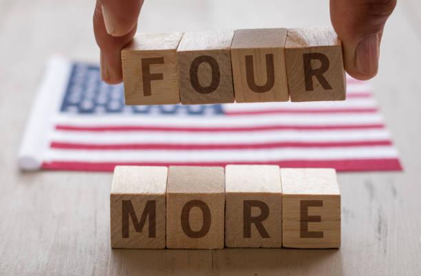 четыре больше концепции на деревянных блоков пальцы проведения четыре с сша флагом - biden стоковые фото и изображения