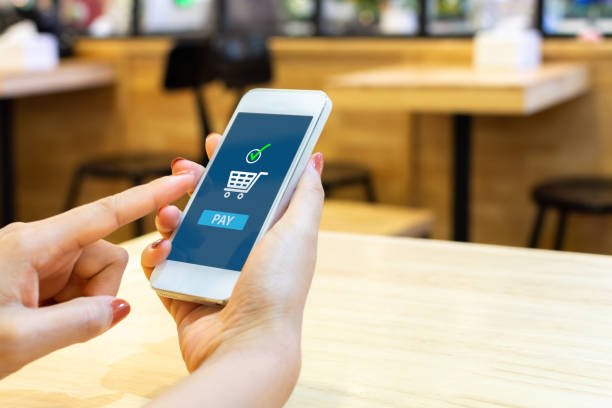concept online payment mobile technology. hand of female using smartphone touching pay button mobile banking application in restaurant - commercio elettronico foto e immagini stock