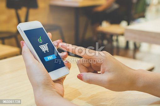 istock Concept online payment mobile technology. Hand of female using smartphone touching pay button mobile banking application in restaurant 963361728