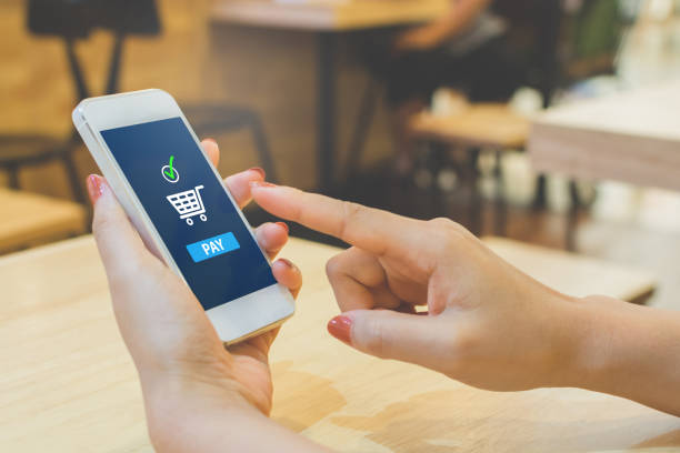 concept online payment mobile technology. hand of female using smartphone touching pay button mobile banking application in restaurant - app store stock photos and pictures