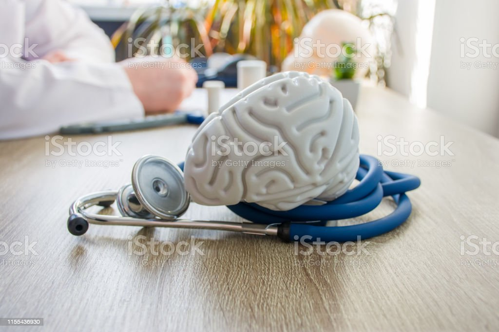 Concept photo of diagnosis and treatment of brain nervous. In foreground is model of brain near stethoscope on table in background blurred silhouette doctor at table, filling medical documentation Concept photo of diagnosis and treatment of brain nervous. In foreground is model of brain near stethoscope on table in background blurred silhouette doctor at table, filling medical documentation Analyzing Stock Photo