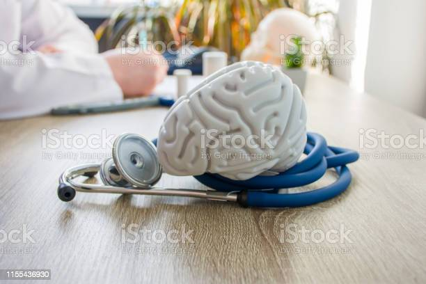 Concept Photo Of Diagnosis And Treatment Of Brain Nervous In Foreground Is Model Of Brain Near Stethoscope On Table In Background Blurred Silhouette Doctor At Table Filling Medical Documentation Stock Photo - Download Image Now