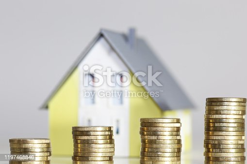 Concept photo with model house and money coins
