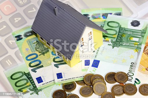 Concept photo with model house, euro bank notes and house keys