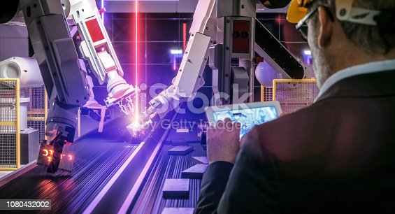 istock Smart automation industry robot in action welding metall while engineer uses his remote control table pc- industry 4.0 concept 1080432002
