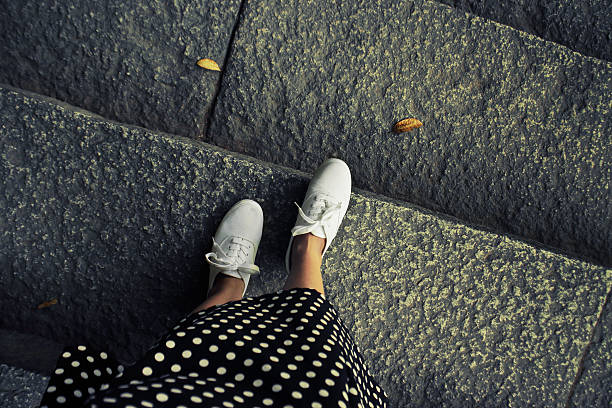 concept picture of legs walking, vintage toned color image. self - flat shoe stock pictures, royalty-free photos & images
