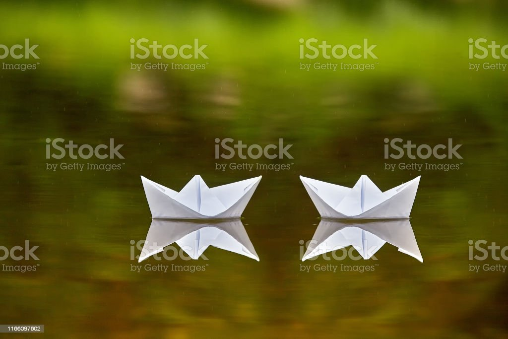 Two paper boats are drifting on th esurface of water as a symbol of...