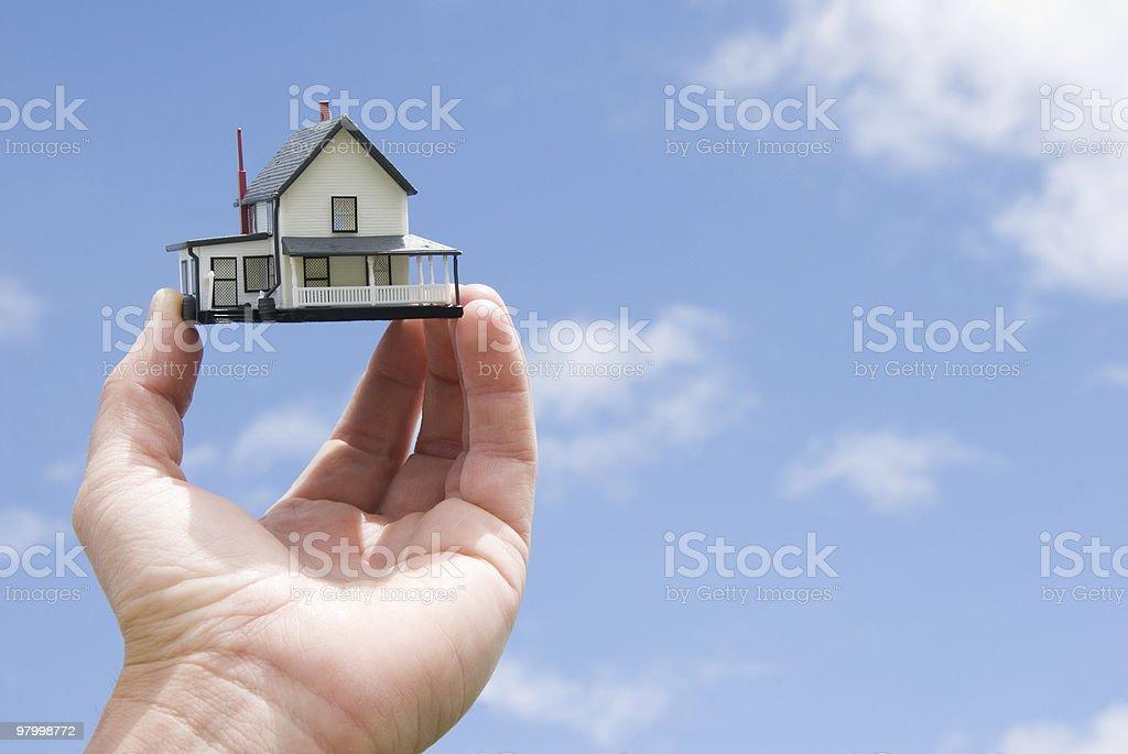 Conceito de Bens Imóveis: Mão segurando uma casa foto royalty-free