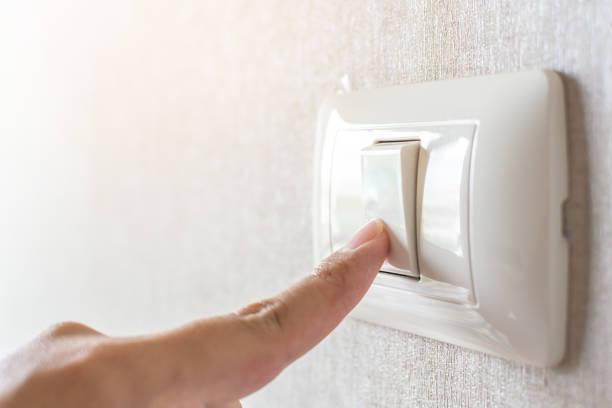 concept d'économiser de l'énergie. interrupteur de main - commutateur photos et images de collection
